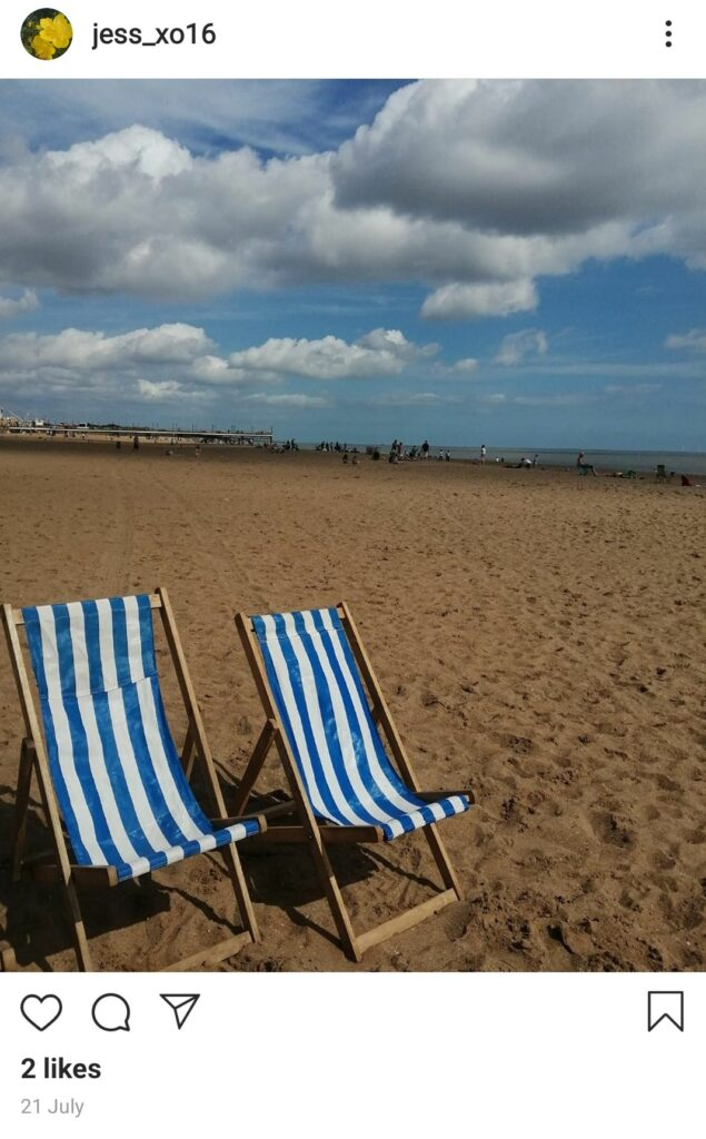 Screen capture of Jess' Instagram post of a two deck chairs in the foreground and a sandy beach and blue sky in the background.